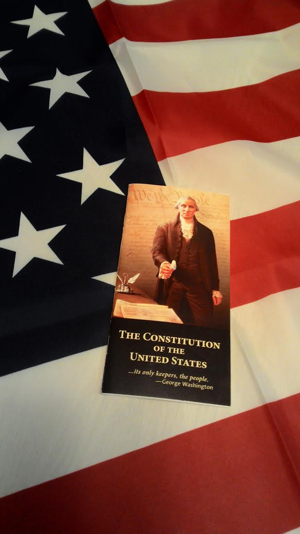 USA flag with a booklet of the Constitution of the United States